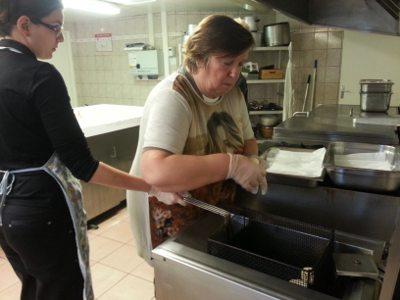 Elodie et la résidente préparent les beignets